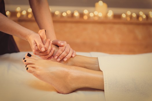 Feet with black nail polish being massaged on a white massage table.
